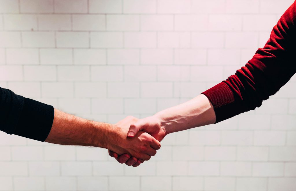 photo représentant deux personnes se serrant la main pour faire un accord